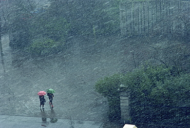 Two lone figures with umbrellas caught in rain storm, Dublin, Republic of Ireland, Europe - 508-20443