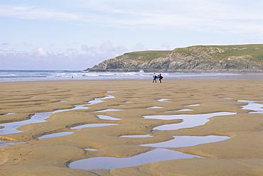 Surfers walking on beach, Holywell Bay, Cornwall, England, United Kingdom, Europe