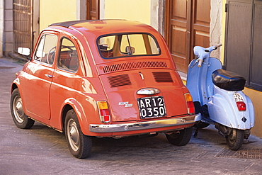 Fiat 500 car and old blue scooter parked together in back street, Tuscany, Italy, Europe