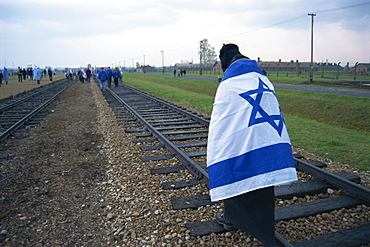 Youngster wrapped in flag walking on rail, Birkenau Concentration Camp, Oswiecim, Malopolska, Poland, Europe