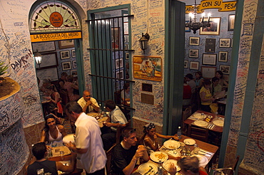 La Bodeguita del Medio restaurant, with signed walls and people eating at tables, Habana Vieja, Havana, Cuba, West Indies, Central America