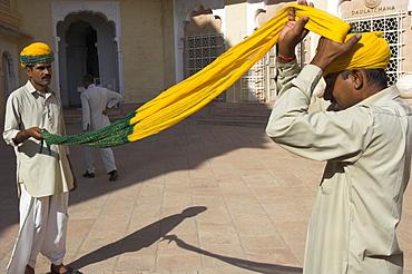 Guard winding his yellow and green turban, Moti Mahal courtyard, Meherangarh fort, Jodhpur, Rajasthan state, India, Asia