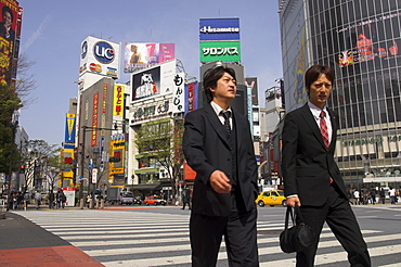 Two well dressed young men walking on zebra crossing with advertising posters and huge video screen in background, Shibuya, Tokyo, Honshu, Japan, Asia