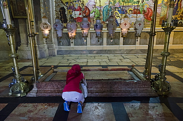 Woman prostrating at the Stone of Anointing. Holy Sepulchre. Jerusalem Old City, Israel, Middle East