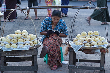 Young woman selling apples from a portable stall in the streets of Yangon (Rangoon), Myanmar (Burma), Asia