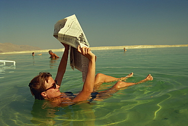 Woman reading a newspaper whilst floating in the Dead Sea, Israel, Middle East