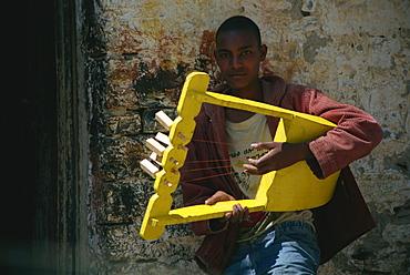 Boy playing handmade instrument, Mekele, Ethiopia, Africa