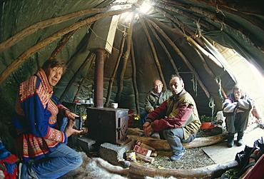 Sami man (Lapplander) inside laavo (tent), drinking moonshine, Finnmark, Norway, Scandinavia, Europe