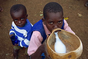 Portrait of young boys drinking goat's milk from gourd, Kenya, East Africa, Africa