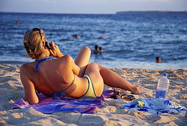 Woman relaxing on Bondi Beach at sundown, using a mobile phone, New South Wales, Australia, Pacific