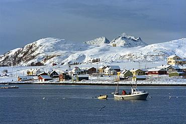 Fishing boat leaving harbour on Kvaloya Island, Arctic Norway, Scandinavia, Europe