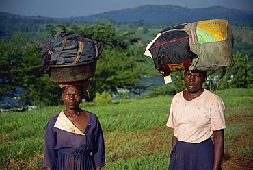 Heavy loads of washing carried on head to be washed in river, Uganda, East Africa, Africa