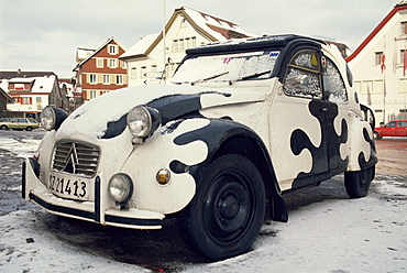 2CV car painted crazy cow, covered in snow
