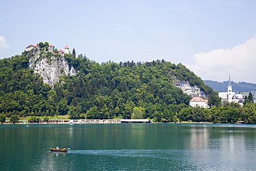 Traditional wooden pletnja (rowing boat) to ferry tourists to St. Mary's Church of Assumption on the islet beyond, Lake Bled, Slovenia, Europe
