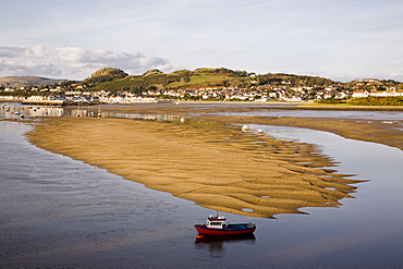 Red boat by exposed rippled sandbank on Conwy River estuary at low tide, with Deganwy beyond, Conwy, Wales, United Kingdom, Europe