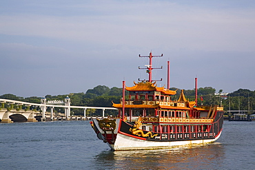 Old Chinese junk used as tour boat for tourist harbour cruise, with road bridge and new monorail to Sentosa Island beyond, Keppel Channel, Singapore, Southeast Asia, Asia