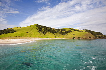 View back to Waewaetorea Island recreational reserve with sandy beach across clear green blue sea on Pacific coast, Bay of Islands, Northland, North Island, New Zealand, Pacific