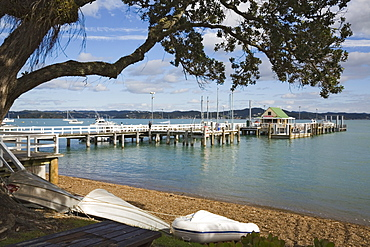 Upturned boats on beach with pier to wharf in bay framed by Pohutukawa tree branches, Russell, Bay of Islands, Northland, North Island, New Zealand, Pacific