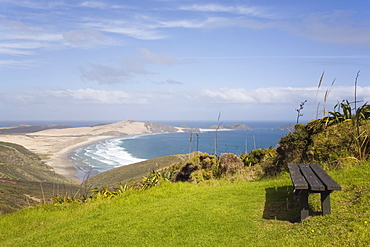 Bench by Cape Reinga Coastal Walkway on cliff top with view to Te Werahi Strand beach and Cape Maria Van Diemen Point, Aupori Peninsula, Northland, North Island, New Zealand, Pacific