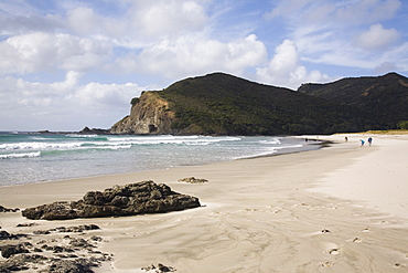 Tapotupotu Bay sandy beach with rolling waves and rocky headland on Pacific east coast, Aupori Peninsula, Northland, North Island, New Zealand, Pacific