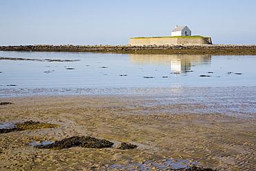 The 12th century Llangwyfan church on small tidal island reflected in calm sea. Porth Cwyfan. Aberffraw. Anglesey, North Wales, United Kingdom, Europe