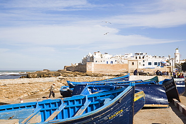 Small wooden fishing boats on seafront with white buildings of the Medina beyond, Essaouira, formerly Mogador, Morocco, North Africa, Africa