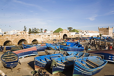 Blue boats in fishing port outside fortified town walls on west coast, Essaouira, Morocco, North Africa, Africa