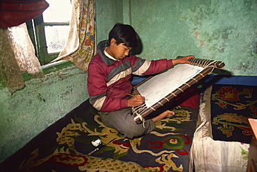 Portrait of a young Tibetan Thangka painter, sitting on a carpet indoors, tangkha paintings used for visualisation in Buddhist meditation, in Darjeeling, India, Asia