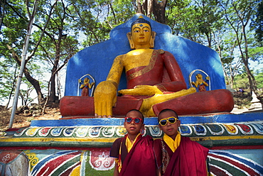 Thupten's twin monks, wearing sunglasses in front of a statue of the Buddha, outdoors, at the Swayambunath Stupa in Kathmandu, Nepal, Asia