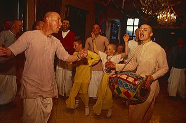 Portrait of a group of Hare Krishna devotees indoors dancing and playing a drum, England, United Kingdom, Europe