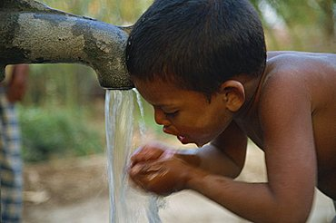 Head and shoulders side view portrait of a young Bangladeshi boy drinking from water pump in a village in Bangladesh, Asia