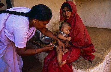 Portrait of an Indian mother holding her baby whilst the child receives a vaccination from an aid project worker, Bangalore, India, Asia