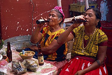 Portrait of two Mexican women in traditional clothing, drinking bottled beer, sitting at a table, Mexico, North America