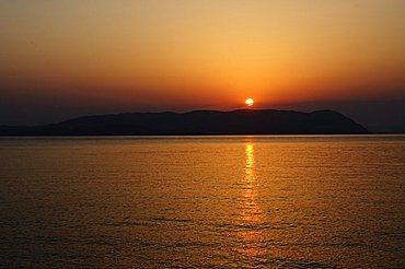 Sunset over the Aegean, taken from Loutraki, Skopelos, with Skiathos in background, Sporades Islands, Greek Islands, Greece, Europe