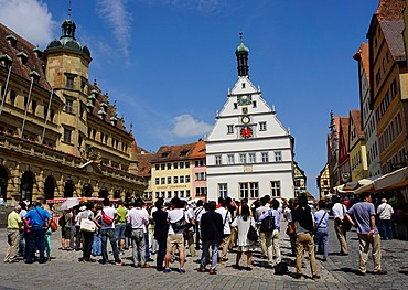 Tourists waiting for the clock to strike on the City Counsellors Tavern in the market square in Rothenburg ob der Tauber, Romantic Road, Franconia, Bavaria, Germany, Europe