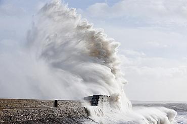 Waves crash against the harbour wall at Porthcawl, Bridgend, Wales, United Kingdom, Europe
