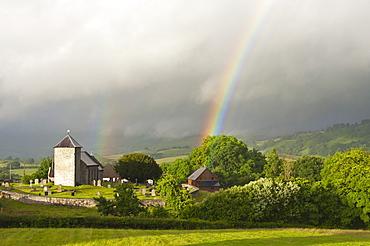 A rainbow over St. David's Church in the tiny Welsh hamlet of Llanddewir Cwm, Powys, Wales, United Kingdom, Europe