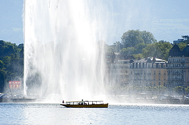 A water taxi passes by the Jet d'Eau at Lac Leman, Geneva, Switzerland, Europe