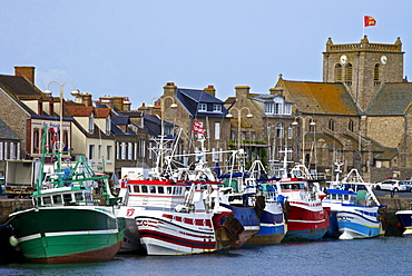 Fishing boats and harbour, and 17th century church in the background, Barfleur, one of the loveliest French village, Cotentin, Normandy, France, Europe