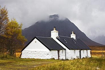 Black Rock Cottage and Buachaille Etive Moor with rain approaching, Rannoch Moor, near Glencoe, Highlands, Scotland, United Kingdom, Europe