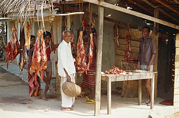 Meat for sale at a butchers stall, and Sri Lankan men looking at the camera, near Colombo, Sri Lanka, Asia