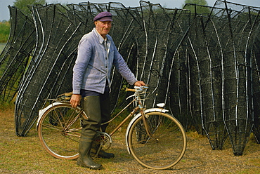 Portrait of a French eel fisherman on his bicycle looking at the camera, with fish traps behind, at the Lac de Grand Lieu in Western Loire, France, Europe