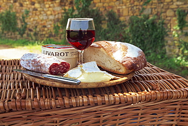 Still life of bread, cheese, glass of red wine and sausage, picnic lunch on top of a wicker basket, in the Dordogne, France, Europe