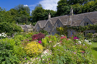 Traditional Cotswold stone cottages with colourful flower gardens, Bibury, Gloucestershire, Cotswolds, England, United Kingdom, Europe