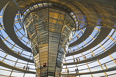 Visitors walk up a spiral ramp around the cone shaped funnel in the dome cupola, which has 360 glass mirrors reflecting light into the Plenary chamber of the Reichstag building, designed by Sir Norman Foster, Berlin, Germany, Europe