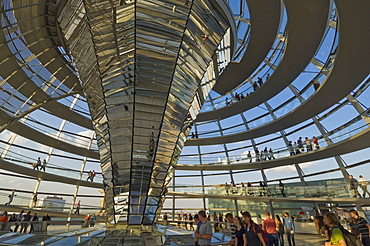 Visitors walk up a spiralling ramp around the cone shaped funnel in the dome cupola, which has 360 glass mirrors reflecting light into the Plenary chamber of the Reichstag building, designed by Sir Norman Foster, Berlin, Germany, Europe