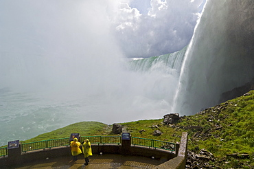Two tourists in yellow raincoats in the spray of the Horseshoe Falls waterfall whilst on the Journey under the Falls tour at Niagara Falls, Ontario, Canada, North America