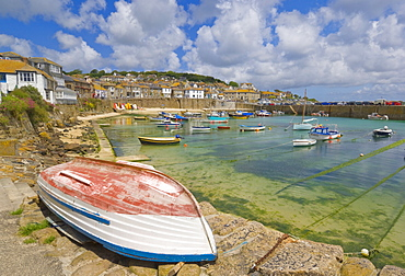 Small unturned boat on the quay and small boats in the enclosed harbour at Mousehole, Cornwall, England, United Kingdom, Europe