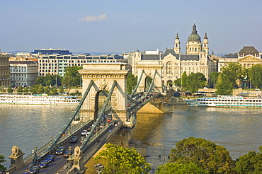 Traffic driving over the River Danube, on The Chain Bridge (Szechenyi Lanchid), with the Gresham Hotel and St. Stephen's Basilica dome behind, Budapest, Hungary, Europe