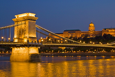 The Chain Bridge (Szechenyi Lanchid), over the River Danube, illuminated at sunset with the Hungarian National Gallery also lit, behind, Budapest, Hungary, Europe